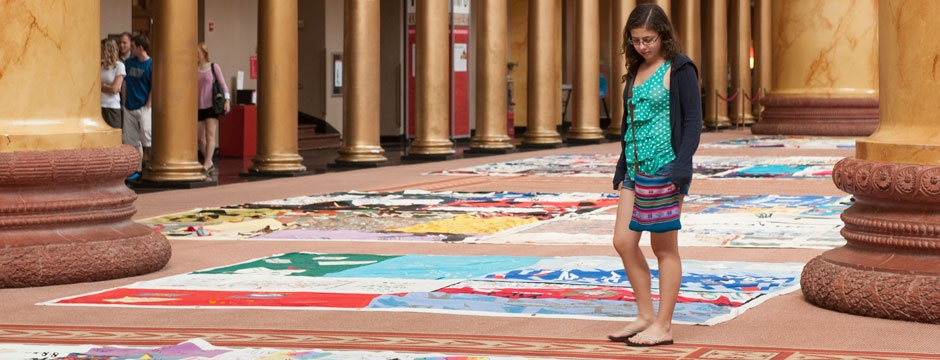 A visitor contemplates squares of the AIDS Memorial Quilt on display in the Museum's Great Hall. Photo by Kevin Allen.